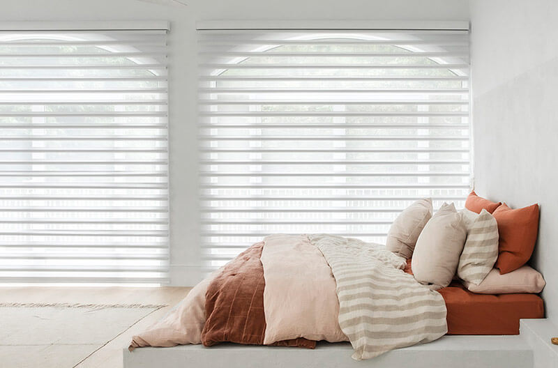 Luxaflex Pirouette Shadings in a bedroom help to create a perfect mixture of privacy andambiance with the unique construction of the plantation shutter like vanes.