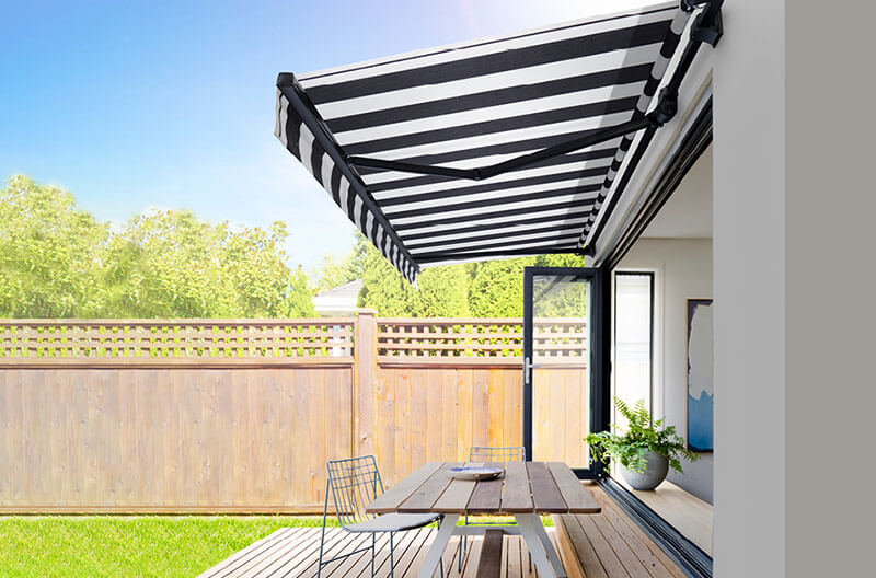 Luxaflex Folding Arm Awning over simple outdoor dining area