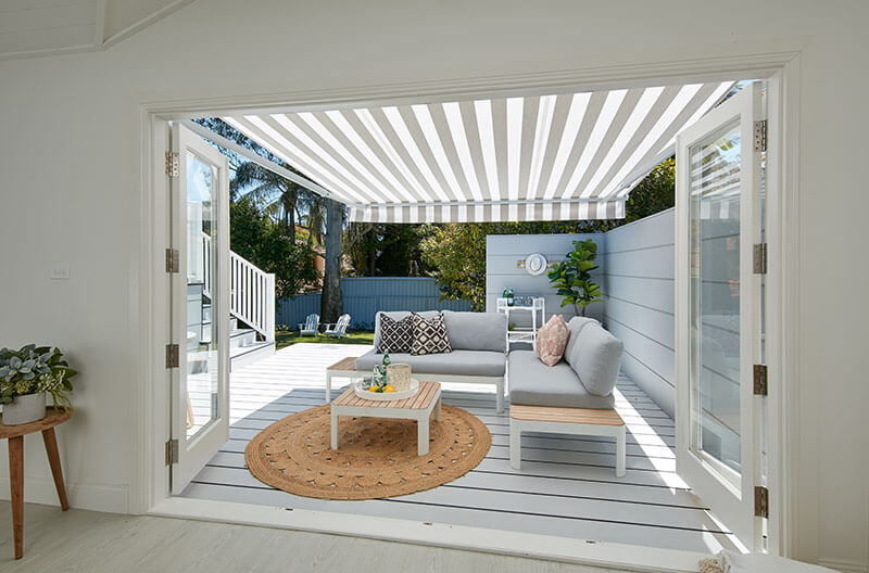 Luxaflex Folding Arm Awning over simple outdoor lounge and entertaining area