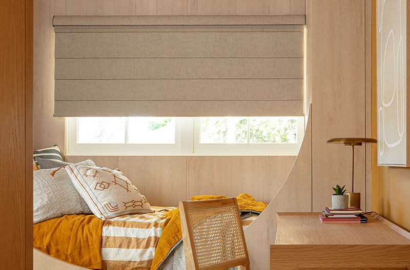 Luxaflex Modern Roman Shades in bedroom setting