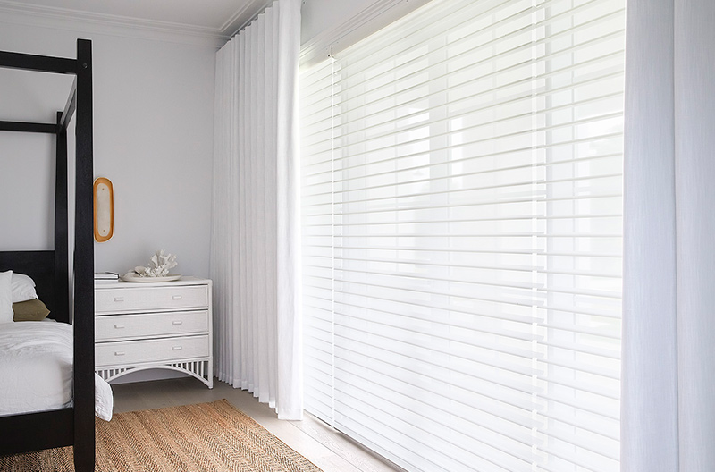 Luxaflex Silhouette Shadings paired with Luxaflex Curtains create a perfect balance of light and privacy within a bedroom.
